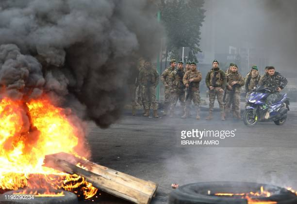 Lebanese Army soldiers stand at attention next to a road blocked by antigovernment demonstrators in the capital Beirut on January 22 2020 Lebanon...