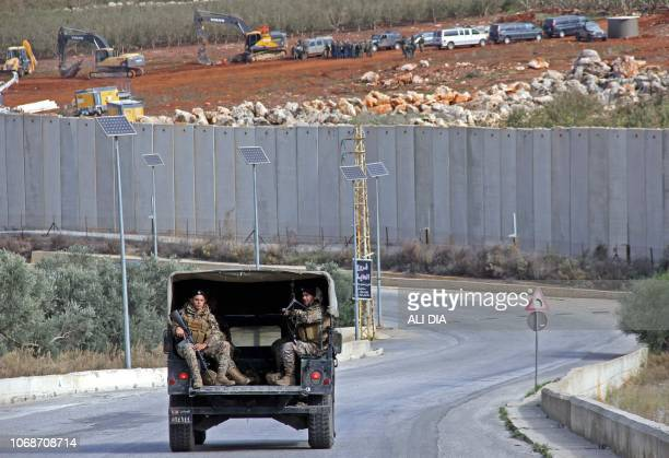 A Lebanese army unit patrols a road on December 5 2018 near the southern Lebanese village of Kfar Kila as members of the Israeli military excavators...
