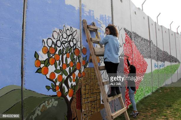 TOPSHOT Lebanese artists draw on a wall on the southern Lebanese border with Israel near Fatima's Gate on December 17 in response to the United...