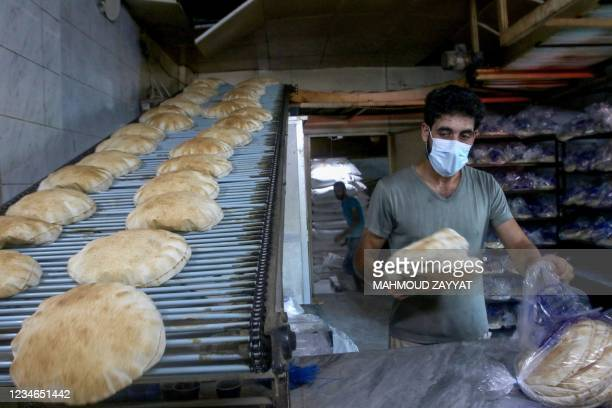 Lebanese bakers bag freshly-baked bread as people queue outside of a bakery in the southern coastal city of Sidon, on August 13 amidst a deepening...