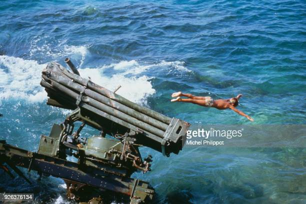 A Lebanese boy dives off the wreckage of a rocket launcher into the Mediterranean