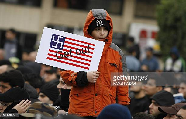A Lebanese boy holds a mock US flag bearing a Nazi swastika instead of stars as he takes part in a rally organised by Hezbollah in the southern...