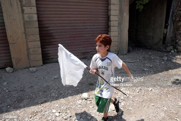Lebanese boy holds a white flag as he tries to flee on August 1 2006 from the village of Aitaroun near Bint Jbail Southern Lebanon after being...