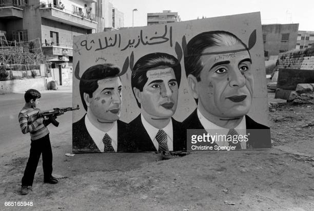 A Lebanese boy points an assault rifle at a large mural of the Gemayel family a family of Christian politicians prominent during the Lebanese Civil...