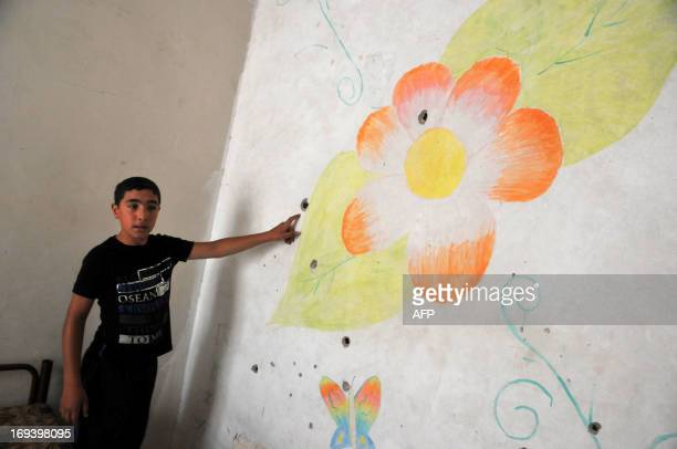A Lebanese boy shows bullet holes on the wall of an apartment in the Bab alTabbaneh district of the northern city of Tripoli on May 24 following...