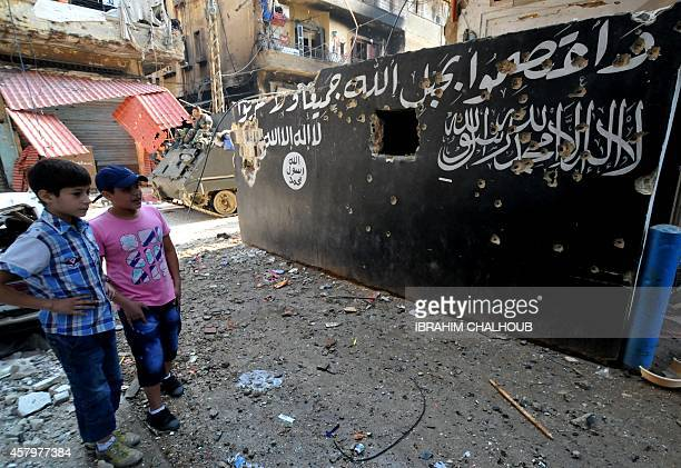 Lebanese boys look at a bulletriddled mural of bearing Islamic texts on a wall in Tripoli's Bab alTabbaneh Sunni neighbourhood on October 28 2014...