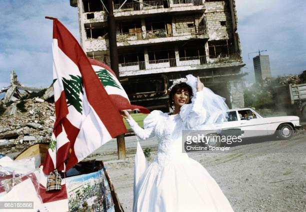 A Lebanese bride poses next to the flag of Lebanon on a street in Beirut Life appears to go on amid the destruction five years after the end of the...