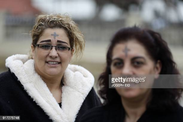 Lebanese Catholic women with the sign of the cross drawn with ash on their foreheads walk out of a Church in Zouk Mikael on February 12, 2018 as...