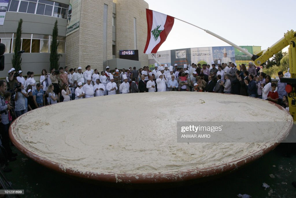 Lebanese chefs celebrate around the largest plate of hummus after setting a new Guinness world record in Beirut on May 8, 2010. The massive hummus serving weighed at 10,452 kilogram (23,520 pounds), the size of Lebanon in square kilometers. This is the third time that the record is broken for the largest hummus serving after Lebanon set the first record in 2009. in January 2010, neighbouring political and culinary rival Israel mashed up over four tonnes of hummus and broke the record.