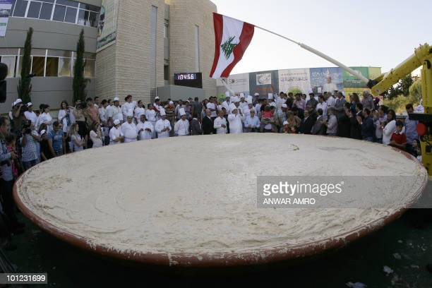 Lebanese chefs celebrate around the largest plate of hummus after setting a new Guinness world record in Beirut on May 8, 2010. The massive hummus...
