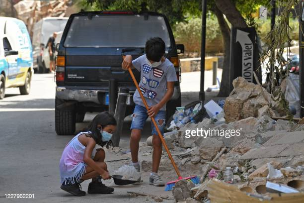 Lebanese children clean debris in Beirut's Gemmayzeh neighbourhood on August 8 four days after a monster explosion killed more than 150 people and...