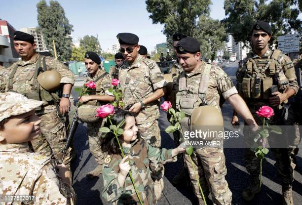 Lebanese children dressed in military uniforms offer roses to soldiers standing guard on a main road east of the capital Beirut on October 22 2019...