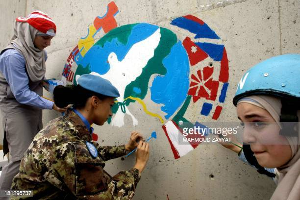 Lebanese children from the neighbourhoods and an Italian peacekeeper paint on a wall of the United Nations Interim Force in Lebanon headquarters...