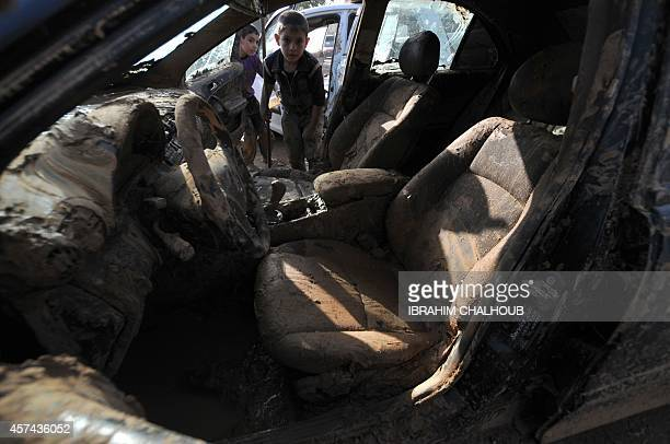 Lebanese children try to clean the mud from the inside of a car that was covered with water due to flooding cause by heavy rains on October 18 in...