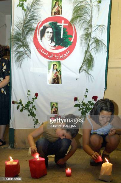 Lebanese Christian children light candles in front of a banner showing the image of Saint Theresa of Lisieux as her coffin carying her remains is...