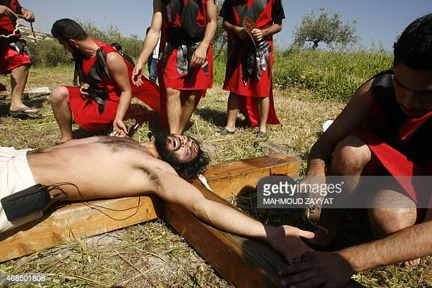 A Lebanese Christian man lays down on a wooden cross during a reenactment of the crucifixion of Jesus Christ during the Good Friday procession on...