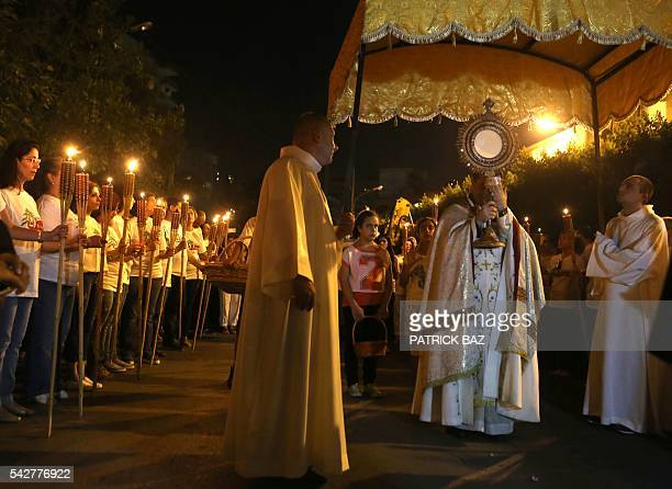 A Lebanese Christian Maronite priest holds a monstrance during a procession in the town of Antelias north east of Beirut on June 24 marking the 35th...