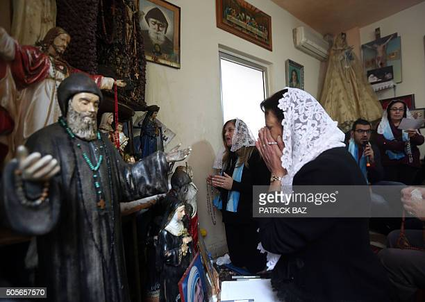 Lebanese Christian women pray in front of statues depicting Christian holy figures during a mystical quasireligious service in an appartment in a...