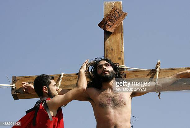 Lebanese Christians one hanging on a wooden cross take part in a reenactment of the crucifixion of Jesus Christ during the Good Friday procession on...