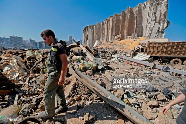 A Lebanese civil defence rescuer walks over the rubble at Beirut port on August 7 three days after a massive blast there shook the Lebanese capital...