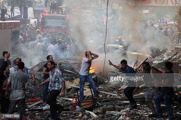 Lebanese civilians and emergency personnel gather at the site of a car bomb between the Bir elAbed and Roueiss neighbourhoods in the southern suburb...