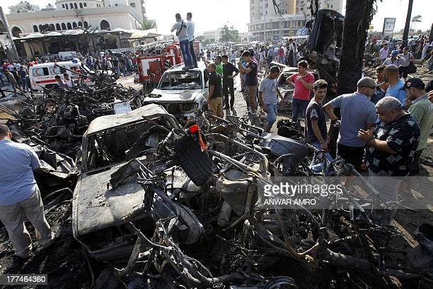 Lebanese civilians gather next to the site of a blast outside the AlTaqwamosque in the northern city of Tripoli on August 23 2013 Car bombs exploded...