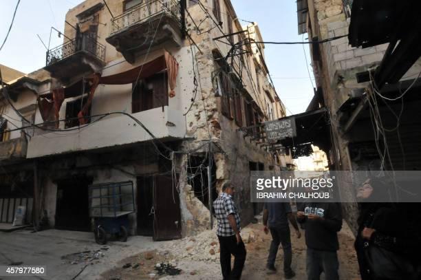 Lebanese civilians walk down a damaged street in Tripoli's Bab alTabbaneh Sunni neighbourhood on October 28 2014 after three days of fierce fighting...