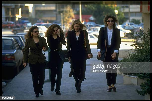 Lebanese college girl chums strolling street, on shopping jaunt, wearing sophisticated, upscale outfits.