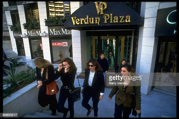 Lebanese college girls in sophisticated outfits leaving behind facade of new, swanky upscale Verdun Plaza shopping mall after shopping jaunt.