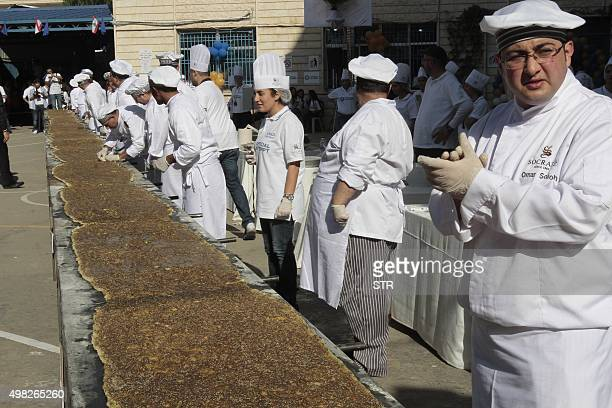 Lebanese competitors prepare a giant manousheh a traditional flatbread garnished with thyme spices sesame and olive oil in a schoolyard in the town...