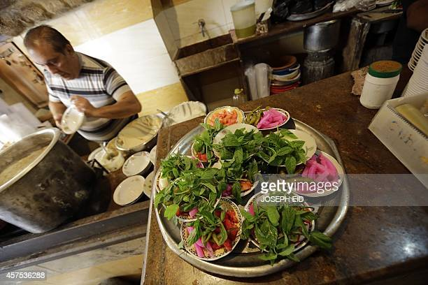 A lebanese cook prepare vegetable side dishes to be served with plates of Fatteh Ful and Hummus at a restaurant in the Lebanese coastal city of...