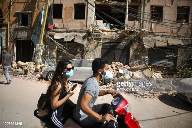 A Lebanese couple drive past the debris of a building in the damaged neighbourhood of Mar Mikhael on August 5 a day after a blast in a warehouse in...