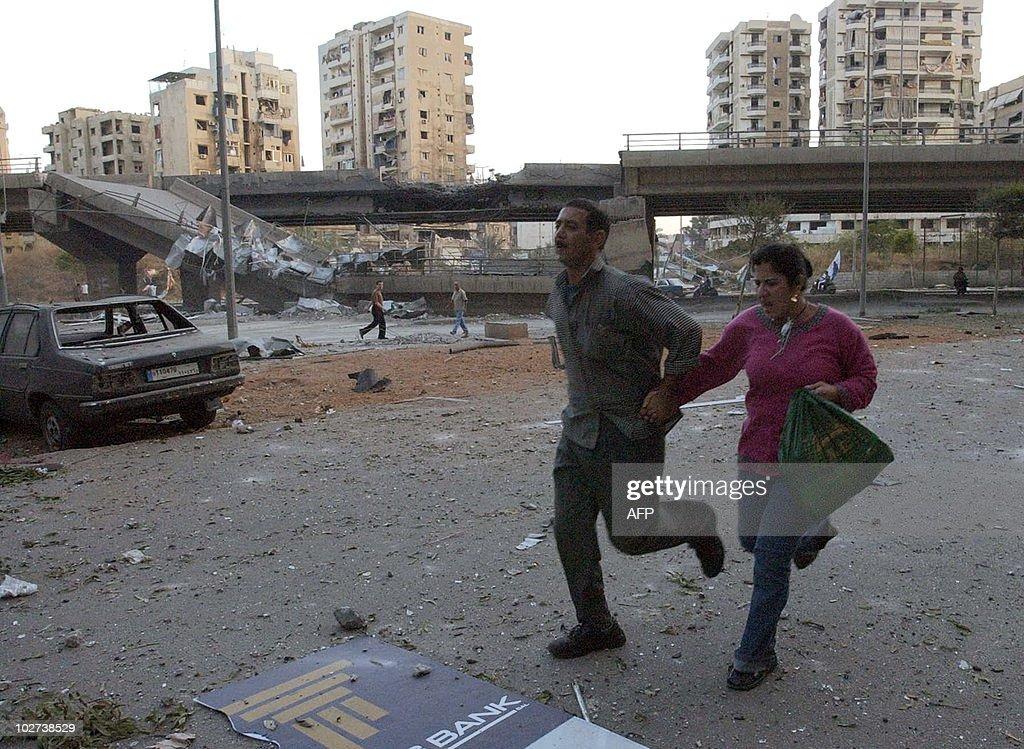 A Lebanese couple run through the street : News Photo