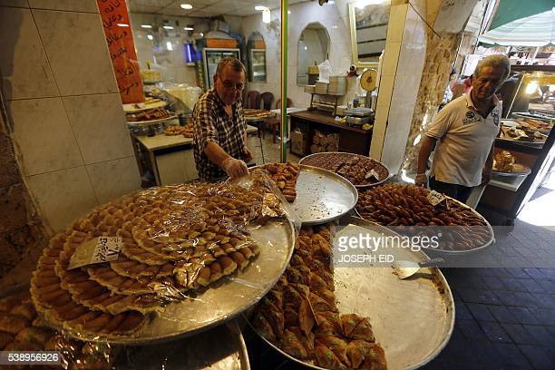Lebanese customers buy sweets at a market in the old part of the Lebanese southern port city of Sidon south of Beirut on June 9 2016 during the...