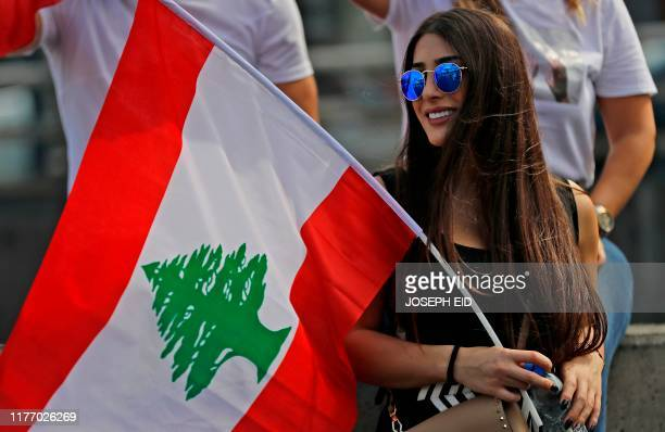 A Lebanese demonstrator attends a demonstration on a highway linking Beirut to north Lebanon in Zouk Mosbeh on October 20 after demonstrations swept...