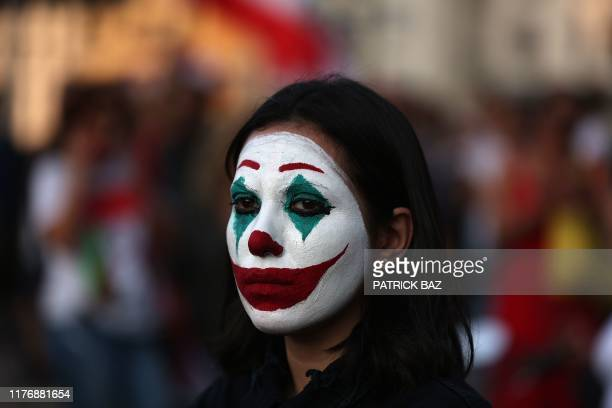 """Lebanese demonstrator, her face painted as DC comic book and film character """"The Joker"""", takes part in a protest in the capital Beirut's downtown..."""