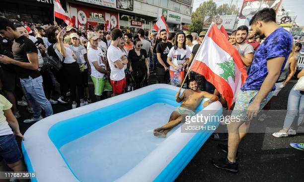 A Lebanese demonstrator holds a national flag as he sits in an inflatable pool on a highway linking Beirut to north Lebanon in Zouk Mosbeh on October...