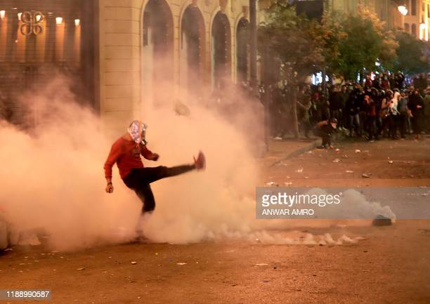 Lebanese demonstrator kicks back a tear-gas canister during clashes with riot police in the capital Beirut on December 15, 2019. - Lebanese police...