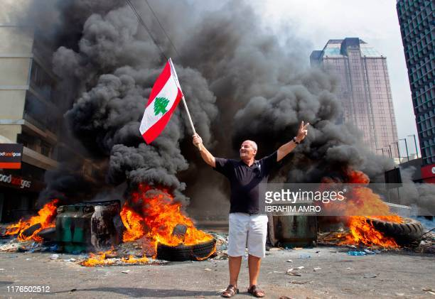 A Lebanese demonstrator waves the national flags in front of a tire fire during a protest against dire economic conditions on October 18 2019 in the...