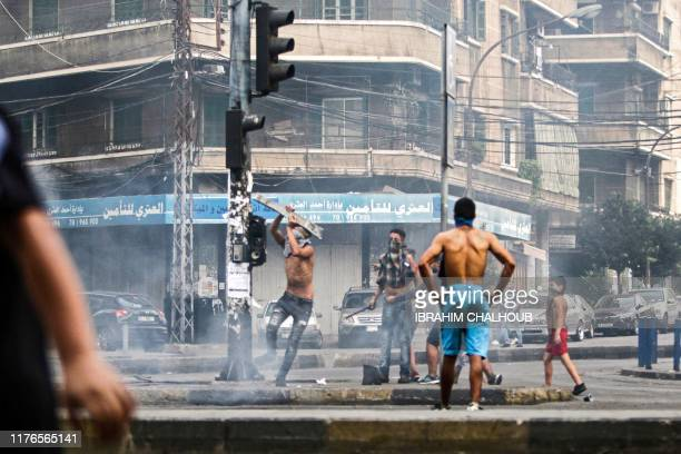 Lebanese demonstrators break traffic lights amidst ongoing protests against dire economic conditions in the northern coastal city of Tripoli on...