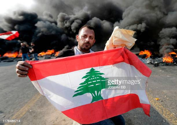 Lebanese demonstrators burn tires and wave their national flag during a protest against dire economic conditions on October 18 2019 on a highway...