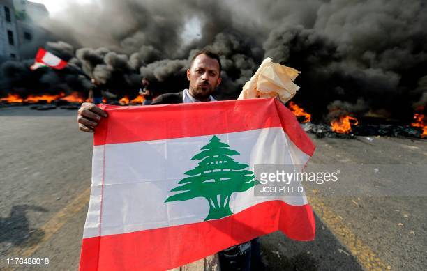 Lebanese demonstrators burn tires and wave their national flag during a protest against dire economic conditions, on October 18, 2019 on a highway...