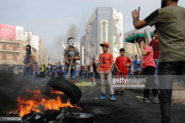 Lebanese demonstrators burn tires during a protest against dire economic conditions, on October 18, 2019 in the northern port city of Tripoli - The...