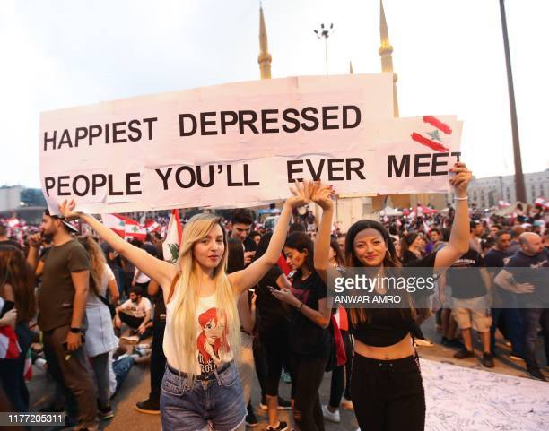 Lebanese demonstrators carry a placard as they take part in a rally in the capital Beirut's downtown district on October 20, 2019. - Thousands...