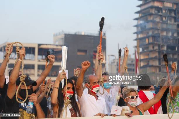 Lebanese demonstrators carry nooses and torches during a demonstration to mark one month since the cataclysmic August 4 explosion that killed 191...