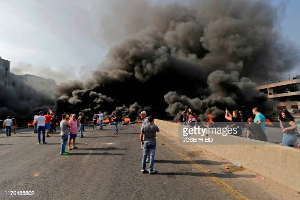Lebanese demonstrators gather on a highway blocked by a tire fire during a protest against dire economic conditions on October 18 2019 in Nahr...