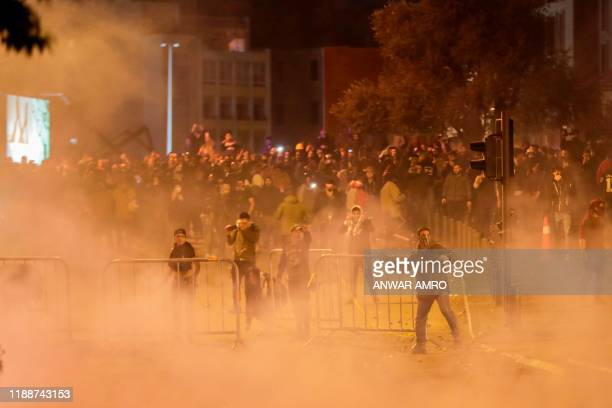 Lebanese demonstrators hurl rocks at riot police during clashes in the capital Beirut on December 14 2019 Lebanese police clashed with antigovernment...