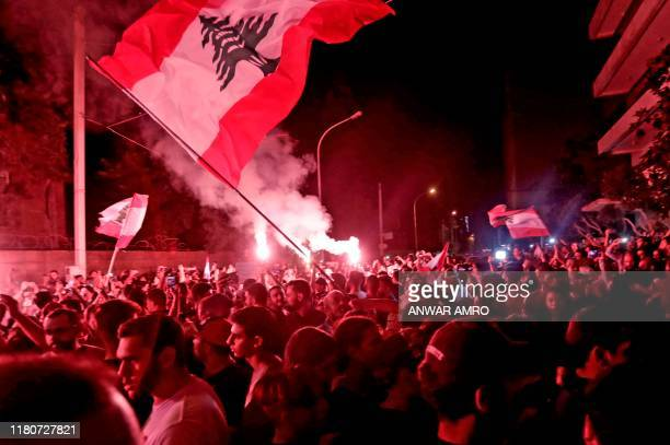 TOPSHOT Lebanese demonstrators light flares and wave national flags as they protest outside the house of former Lebanese prime minister Fouad Siniora...