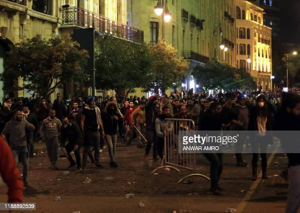 Lebanese demonstrators move a metal barrier during clashes with security forces in the downtown area of the capital Beirut, on December 15, 2019. -...