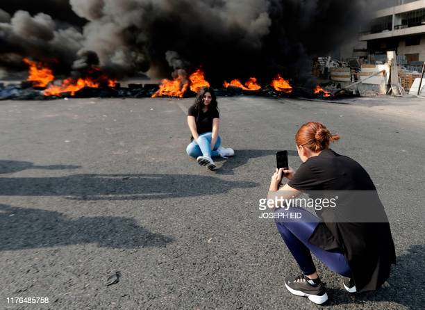 TOPSHOT Lebanese demonstrators pose for pictures in front of a tire fire during a protest against dire economic conditions on October 18 2019 in Nahr...